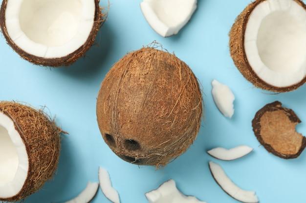 Свежий вкусный кокос на синем фоне, вид сверху