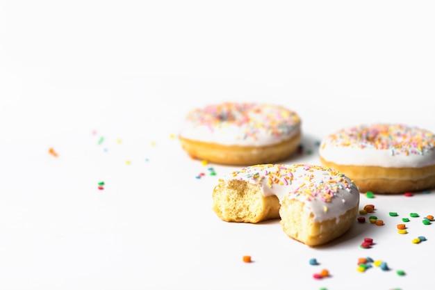 신선한 맛있는 도넛과 흰색 배경에 달콤한 여러 가지 빛깔 된 장식 사탕. 베이커리 개념, 신선한 파이, 맛있는 아침 식사.