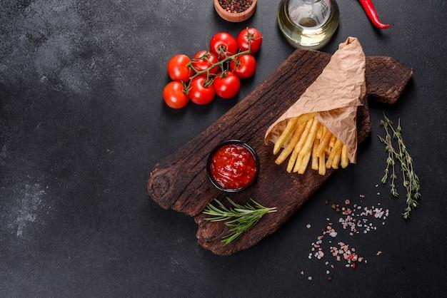 신선한 맛있는 감자 튀김과 나무 커팅 보드에 빨간 소스. 건강에 해로운 음식, 패스트 푸드