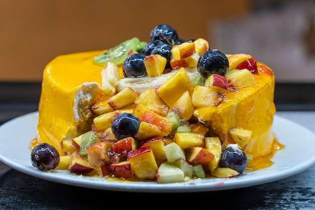 Fresh and tasty fruit cake with grapes, peach, apple, banana and kiwi, close up