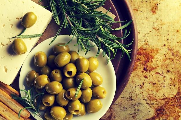 チーズフェタまたはヤギチーズの新鮮なおいしいギリシャ緑のオリーブ。閉じる。地中海料理。トーニング。