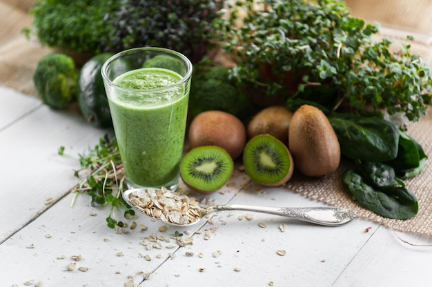 Fresh and tasty green smoothie with ingredients on wooden surface
