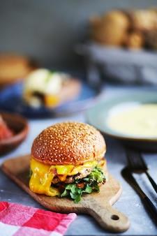 음식 중 신선한 맛있는 햄버거 쇠고기, 치즈, 베이컨 및 야채와 함께 햄버거 샐러드와 근접 햄버거, 보드에 치즈 클래식 햄버거 음식의 날 테이블에 음식입니다 치즈 확산