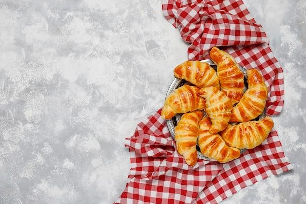 Fresh tasty homemade croissants on grey-white . french pastry