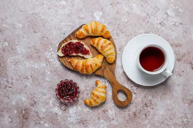 Fresh tasty homemade croissants with raspberry jam on grey-white . french pastry