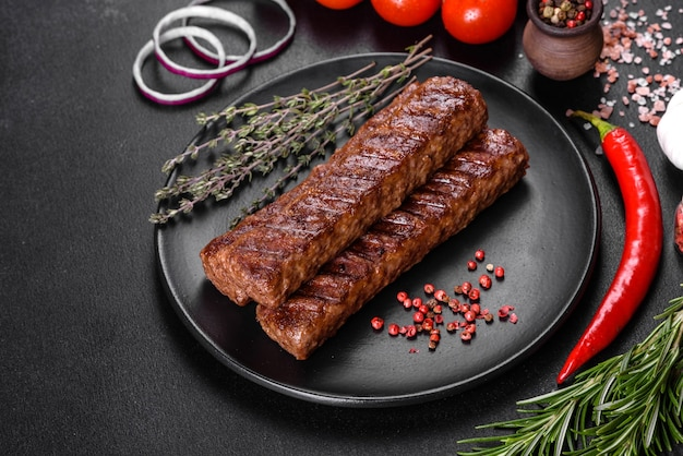Свежий вкусный шашлык на гриле со специями и зеленью. мясное блюдо на гриле