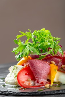 ルッコラ、パルマハム、オリーブオイル、ハーブ入りの新鮮なおいしいperサラダ。秋、冬の健康食品