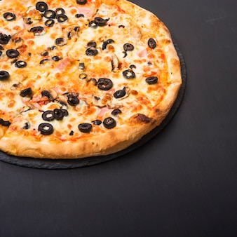 Fresh tasty pizza with olives and meat topping on slate over dark backdrop