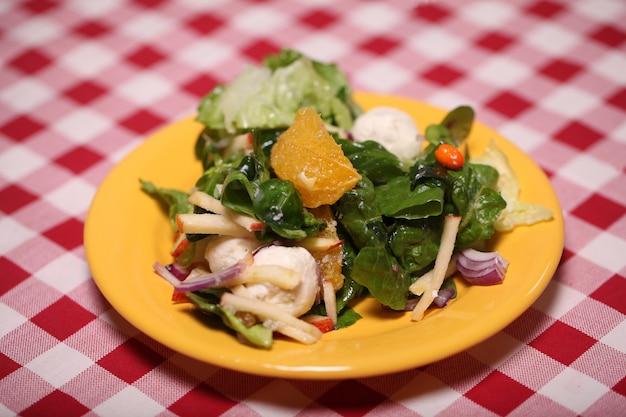 Свежий вкусный салат в тарелке на скатерть