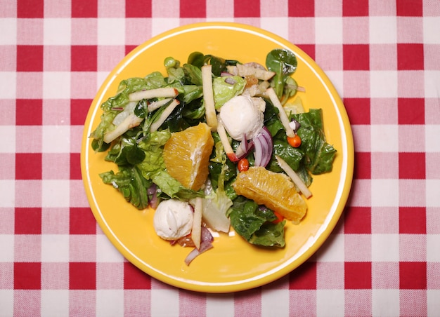 Fresh tasty salad in a plate on a tablecloth