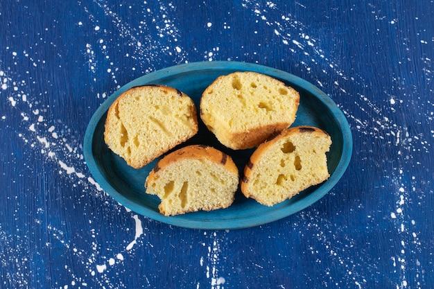 신선한 맛있는 슬라이스 케이크 블루 접시에 배치.