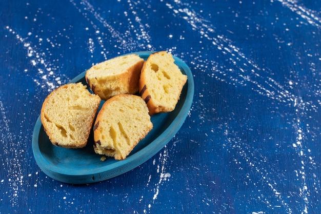 파란색 접시에 신선한 맛 있는 슬라이스 케이크를 배치합니다.