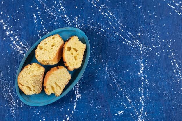 青いプレートに置かれた新鮮なおいしいスライスケーキ