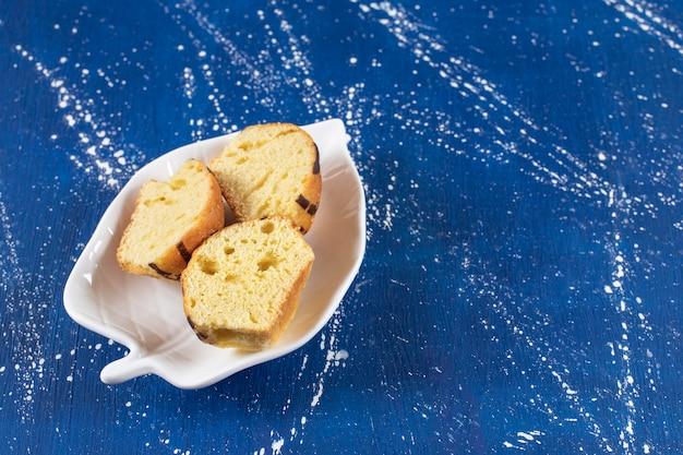 잎 모양의 접시에 신선한 맛있는 슬라이스 케이크를 배치합니다.