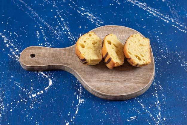 신선한 맛있는 슬라이스 케이크가 나무 판자에 놓여 있습니다.