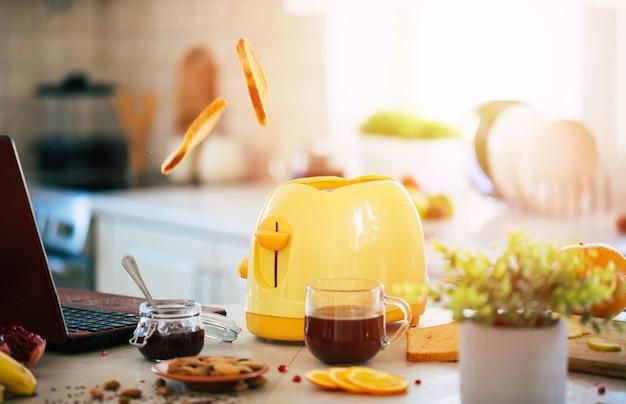 Свежие вкусные ломтики тостов из желтого тостера на красивом кухонном столе дома