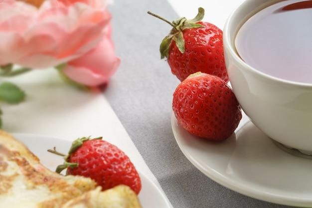 Fresh, tasty strawberries for breakfast on a light background.