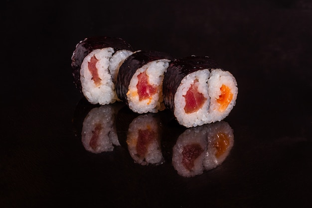 Fresh and tasty sushi on dark background