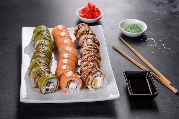 生姜とわさびを添えた龍の形に並べられた新鮮でおいしい巻き寿司。日本料理