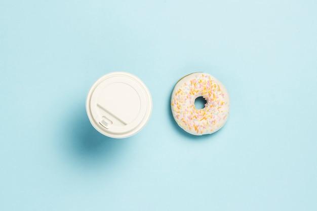 Свежий вкусный сладкий пончик и бумажный стаканчик с кофе или чаем на синем фоне. концепция фаст-фуда, хлебопекарня, завтрак ,. минимализм. плоская планировка, вид сверху.