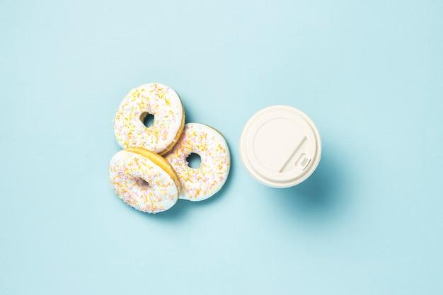 Свежие вкусные сладкие пончики и бумажный стаканчик кофе или чая на синем фоне. концепция фаст-фуда, хлебопекарня, завтрак ,. минимализм. плоская планировка, вид сверху.