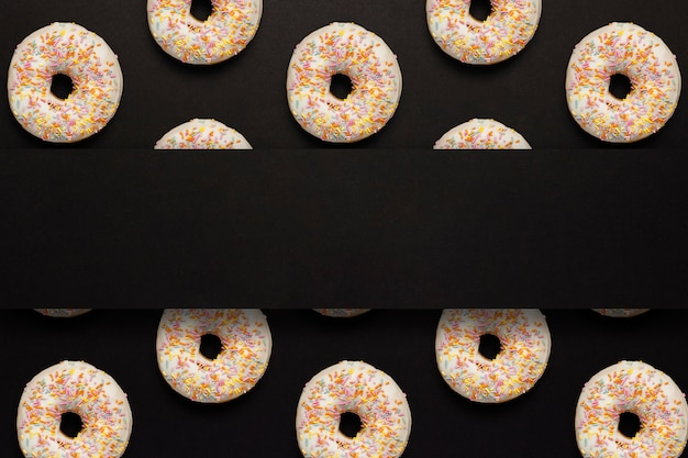 Fresh tasty sweet donuts on a black background.