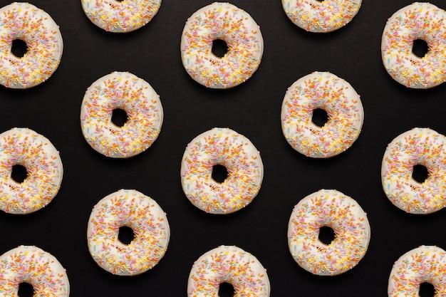 Свежие вкусные сладкие пончики на черном фоне. концепция быстрого питания, пекарня, завтрак, сладости. минимализм. шаблон.