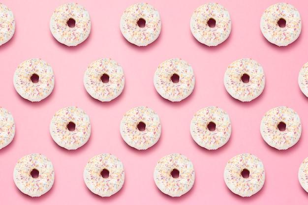 Свежие вкусные сладкие пончики на розовом фоне. шаблон.
