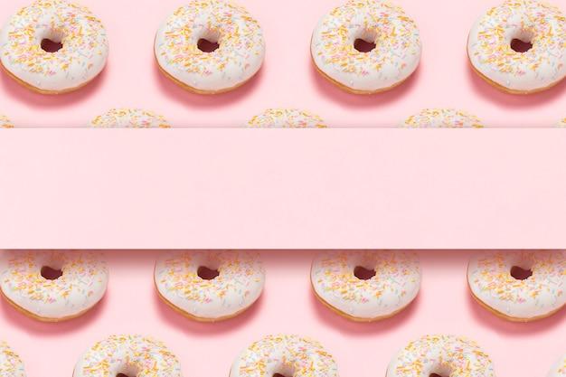 Свежие вкусные сладкие пончики на розовом фоне. место для текста. концепция быстрого питания, пекарня, завтрак, сладости. минимализм. шаблон. плоская планировка, вид сверху, копия пространства.