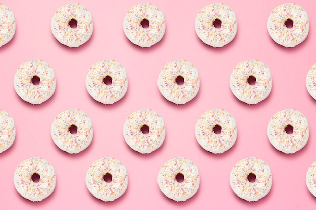 Fresh tasty sweet donuts on a pink background. pattern.