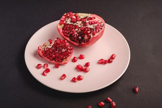 Свежий вкусный сладкий очищенный гранат с красными семенами в розовой тарелке на темно-черном столе