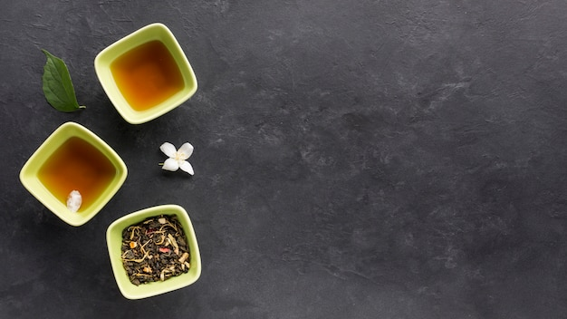 Fresh tea with dried herb and jasmine flower on black surface