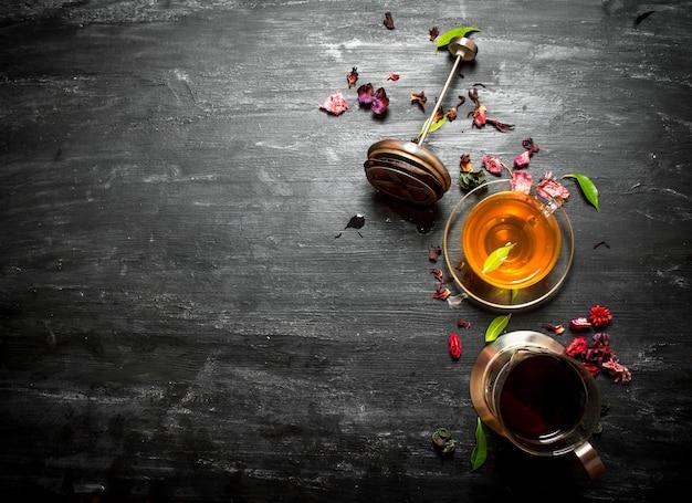 Свежий чай с гранатом и сухофруктами на черном деревянном столе.