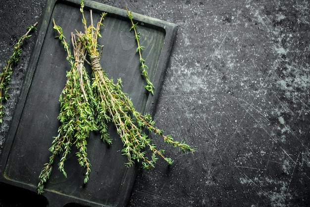 Fresh thyme on cutting board on dark rustic table