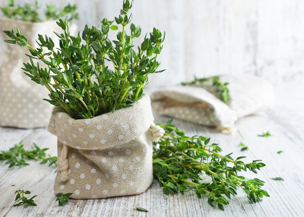 Fresh thyme in decorative pouch on old wooden table