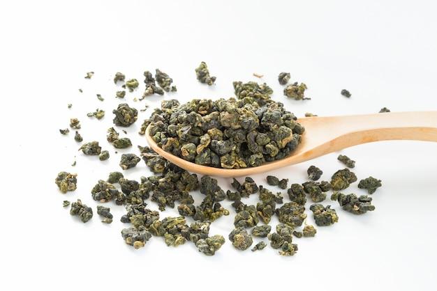 Fresh tieguanyin oolong tea on wooden spoon