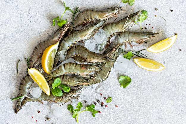 Свежие тигровые креветки с дольками лимона, зеленью и специями на кубиках льда на светло-сером фоне сырые маринованные морепродукты, готовые к приготовлению, вид сверху