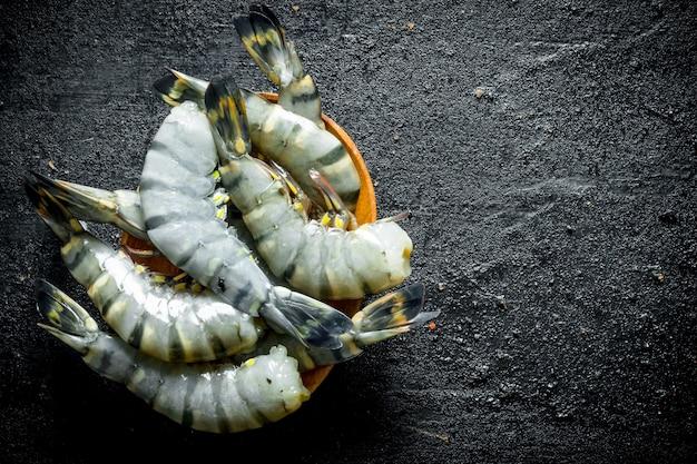 Свежие тигровые креветки на тарелке на деревенском столе
