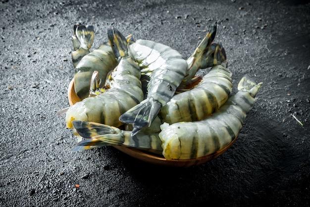 Свежие тигровые креветки на тарелке.