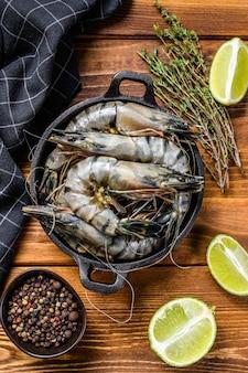 Свежие тигровые креветки, креветки со специями и зеленью на сковороде