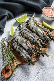 Fresh tiger shrimps, prawns with spices and herbs on a cutting board.