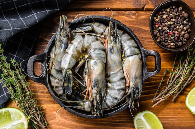 Fresh tiger shrimps, prawns with spices and herbs in a pan.
