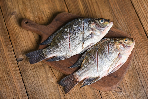 Fresh tilapia fish for cooking food, two raw nile tilapia freshwater fish with salt on wooden wooden board