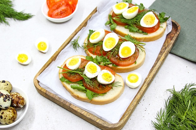 메추라기 달걀 토마토와 녹색 허브를 곁들인 신선한 토스트 샌드위치