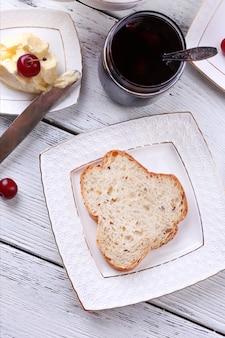 木製のテーブルの上のプレートに自家製バターを入れた焼きたてのトースト