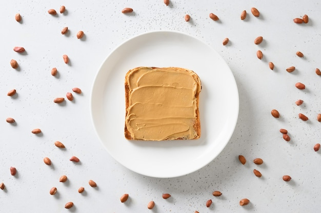 Fresh toast with peanut paste and nuts around on white.