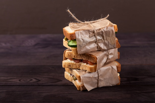 Fresh toast with salmon, cream cheese and vegetables lie in a pile, wrapped in craft paper.