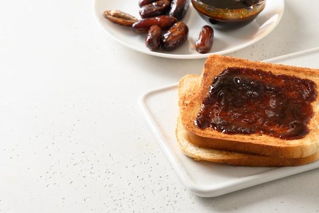 白いテーブルに砂糖なしでナツメヤシのジャムを添えた新鮮なトースト。閉じる。スペースをコピーします。