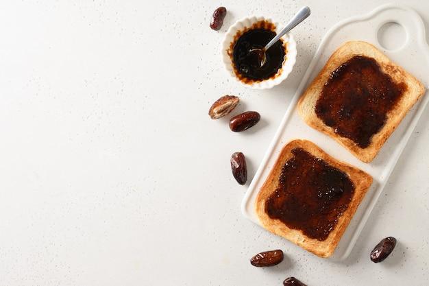 白いテーブルの上に砂糖なしで日付ジャムと新鮮なトースト