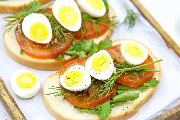 Свежие тосты с перепелиными яйцами, помидорами и зеленью
